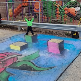 A child poses on one of Shaun Hays' 3D Chalk Art Creations in Humbolt Park during an after school celebration of the Arts.